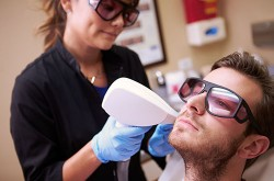 Image of Man Having Laser Treatment At Beauty Clinic