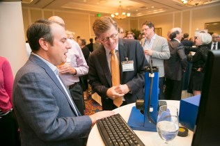 Adam Wax, PhD, Professor of Biomedical Engineering explains to President Price how Lumedica has made Optical Coherence Tomography small and affordable. Photo by Jared Lazarus/Duke Photography