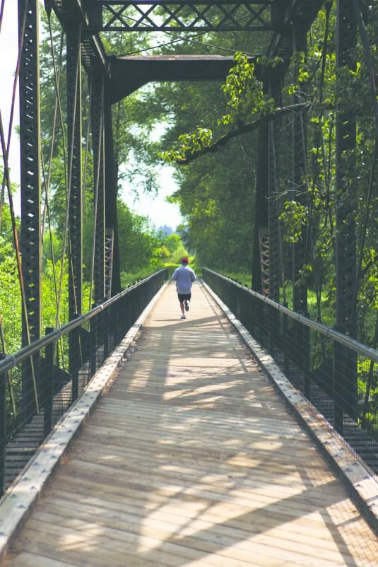 A jogger crosses a bridge across the Chehalis river on the Willapa Hills trail outside of Chehalis.
