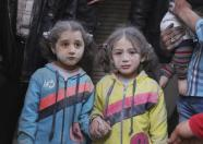 Girls who survived what activists said was a ground-to-ground missile attack by forces of Syria's President Bashar al-Assad, hold hands at Aleppo's Bab al-Hadeed district April 7, 2015. REUTERS/Abdalrhman Ismail