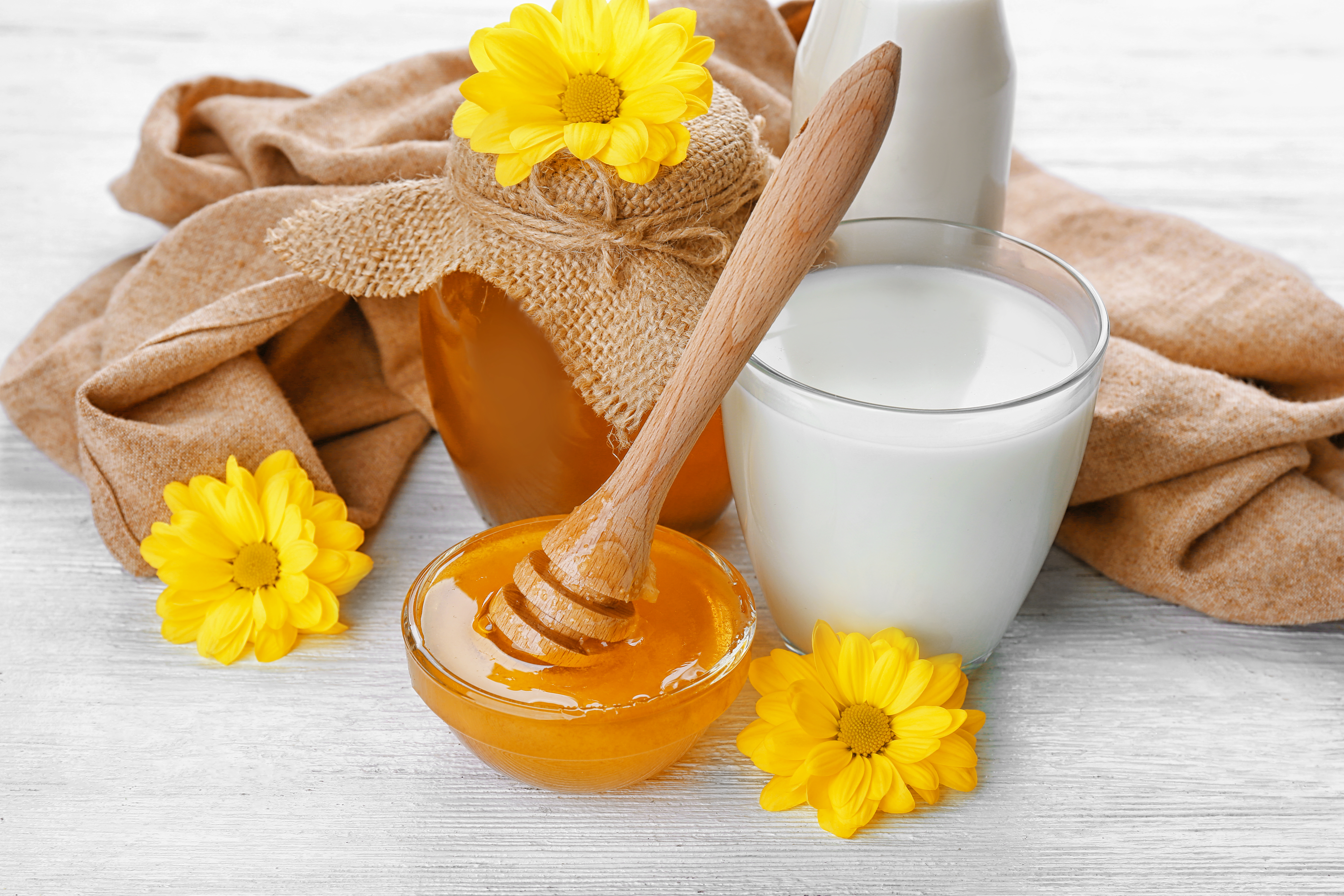 Glass of fresh milk and bowl with golden honey on white wooden table