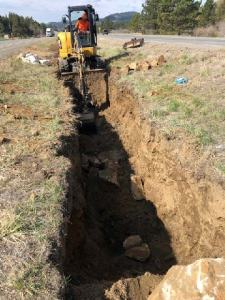 Digging a trench in the median of an interstate highway with a mini excavator