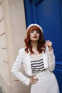 Photographie de Louise Ebel devant une porte bleue