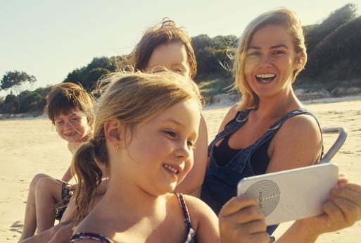 une famille qui se prend en photo à la plage