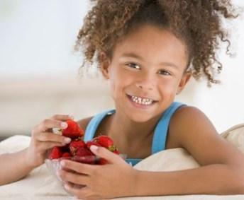 petite fille qui mange des fraises, un fruit de saison estivale