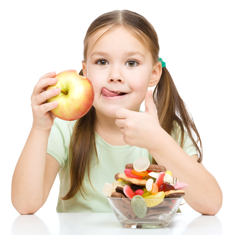 petite fille préfère le fruit (pomme, fruit préféré des français) plutôt que les bonbons