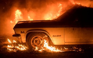 CORRECTS TO JULY FROM JUNE - Flames from a wildfire consume a car near Oroville, Calif., on Saturday, July 8, 2017. Evening winds drove the fire through several neighborhoods leveling homes in its path. (AP Photo/Noah Berger)