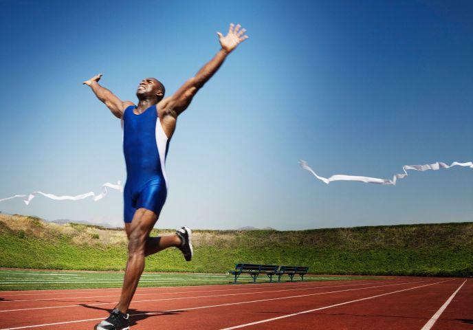 un hombre corriendo alegre cruzando una meta