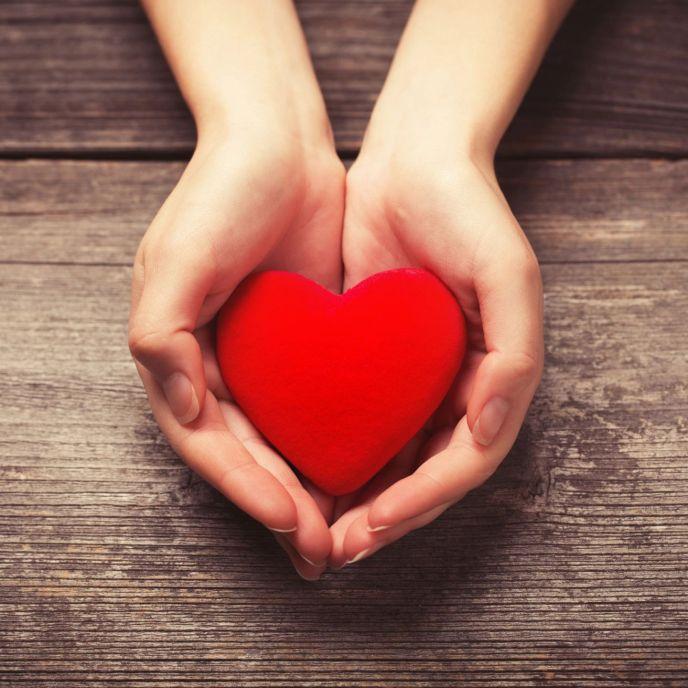 dos manos entregando un símbolo de un corazón