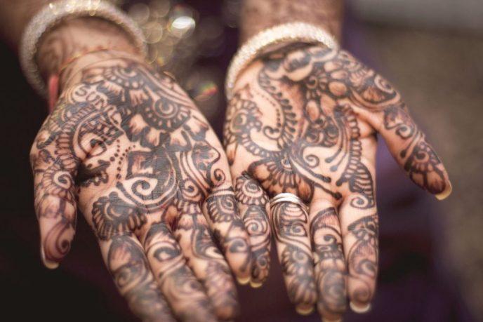 dos manos completamente tatuadas con símbolos de alguna tribu