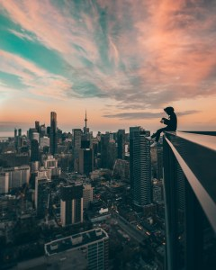person sitting on a ledge overlooking city