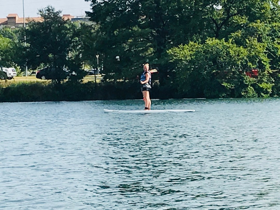 Client paddle boarding on town lake