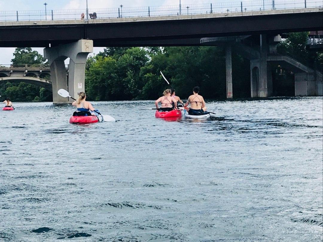 Clients kayaking on town lake heading under the congress bridge