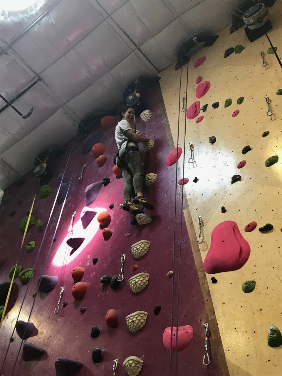 Client indoor rock climbing took a moment to pause just a few feet from the top and pose for a photo