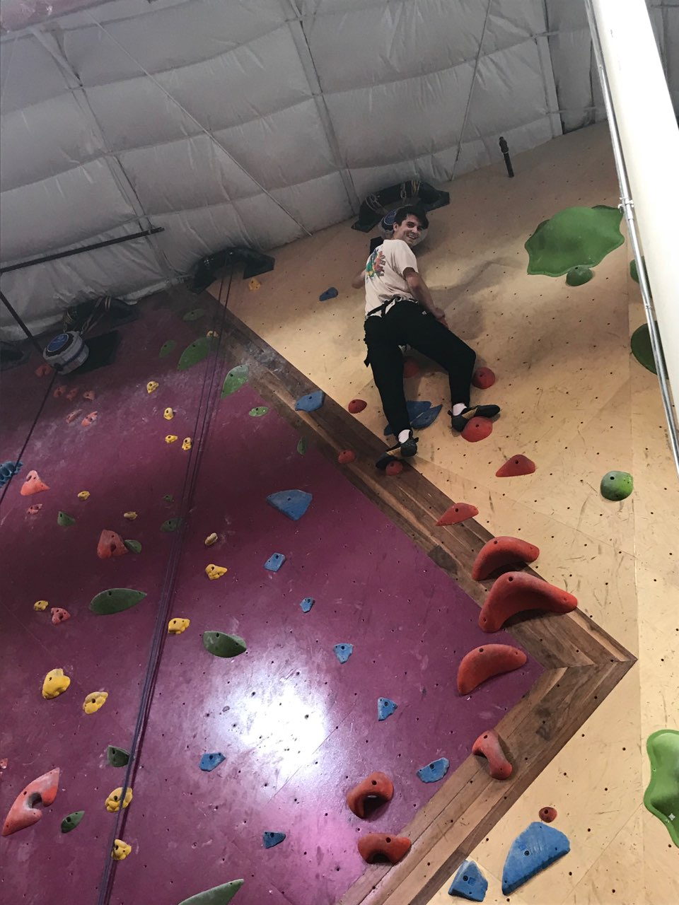 Photo of client indoor rock climbing smiling as he reached the top of the wall
