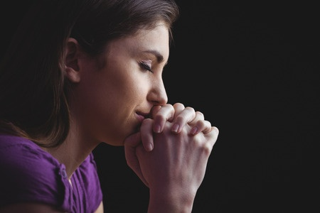 45313084 - woman praying with hands together on black background