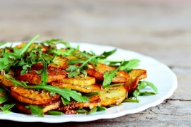 Savory roasted potatoes with arugula on a white plate. Wooden background. Easy vegetable side dish cooked with potatoes and arugula. Warm salad recipe. Vegetarian meal. Closeup