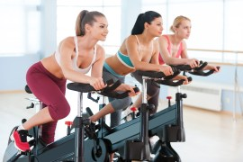 Two attractive young women in sports clothing exercising on gym bicycles ** Note: Shallow depth of field