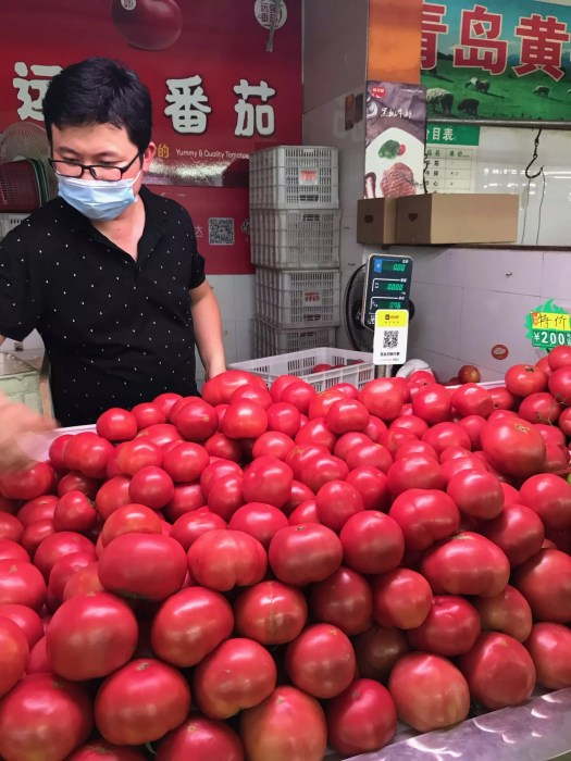 man selling tomatoes in Shanghai wet market