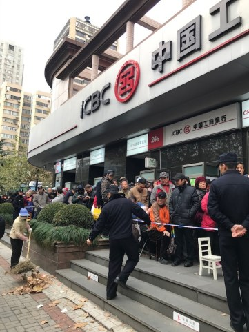 people line up outside a Chinese bank - how to save money for travel a working class guide - onaroadtonowhere.com