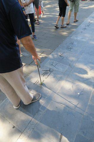 Un vieux monsieur fait de la calligraphie sur le sol avec de l'eau