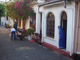 Une femme observe ce qui se passe dans la rue