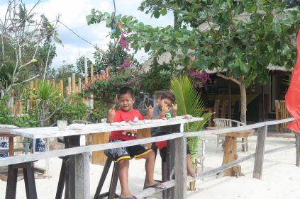 Deux garçons sur la plage, vendant des cailloux pour faire des ricochets. Lors de la photo, un des gamins fait ce geste déplacé...
