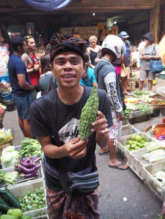 Notre chef cuisiner/guide tenant une courgette à peau de crocodile - Marché de Ubud