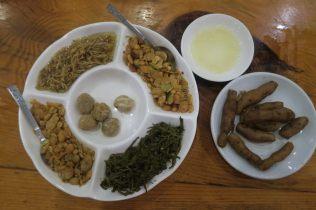 Desserts birmans : sucre à base de jaggery, gingembre mariné, feuille d'algues, cacahuètes et graines de sésame grillées. Racines à tremper dans le beurre salé.