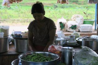 Une jeune femme faisant la cuisine sur le quai d'une gare
