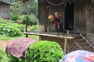 Une mère Pa-O qui balaie devant sa porte