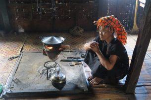 """La mère de notre guide, assise dans sa cuisine, préparant le thé. Elle porte les vétements traditionnels de l'ethnie Pa-O : un ensemble noir et un """"turban"""" de couleur sur la tête"""