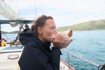 Elise tente de souffler dans le coquillage pour appeler les habitants de la mer...