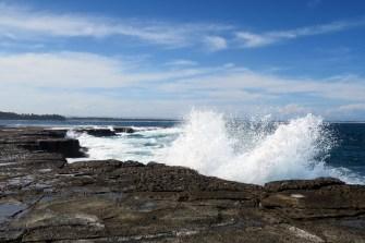 Les vagues se jetent sur les rochers en bas du phare de Norah Head
