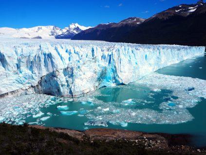 Le front du glacier Perito Moreno. Une énorme plaque de glace vient de s'en séparer : la glace est bleue à l'endroit de la séparation. Dans l'eau flottent les bouts de glace qui viennent de tomber
