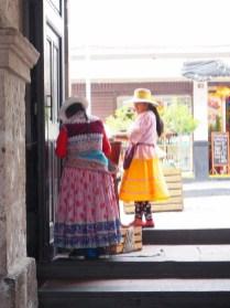 Des femmes en habit traditionnel posent pour les touristes