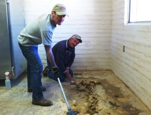 Mike and Don prep the floor in the kitchen annex room to be tiled by the two.