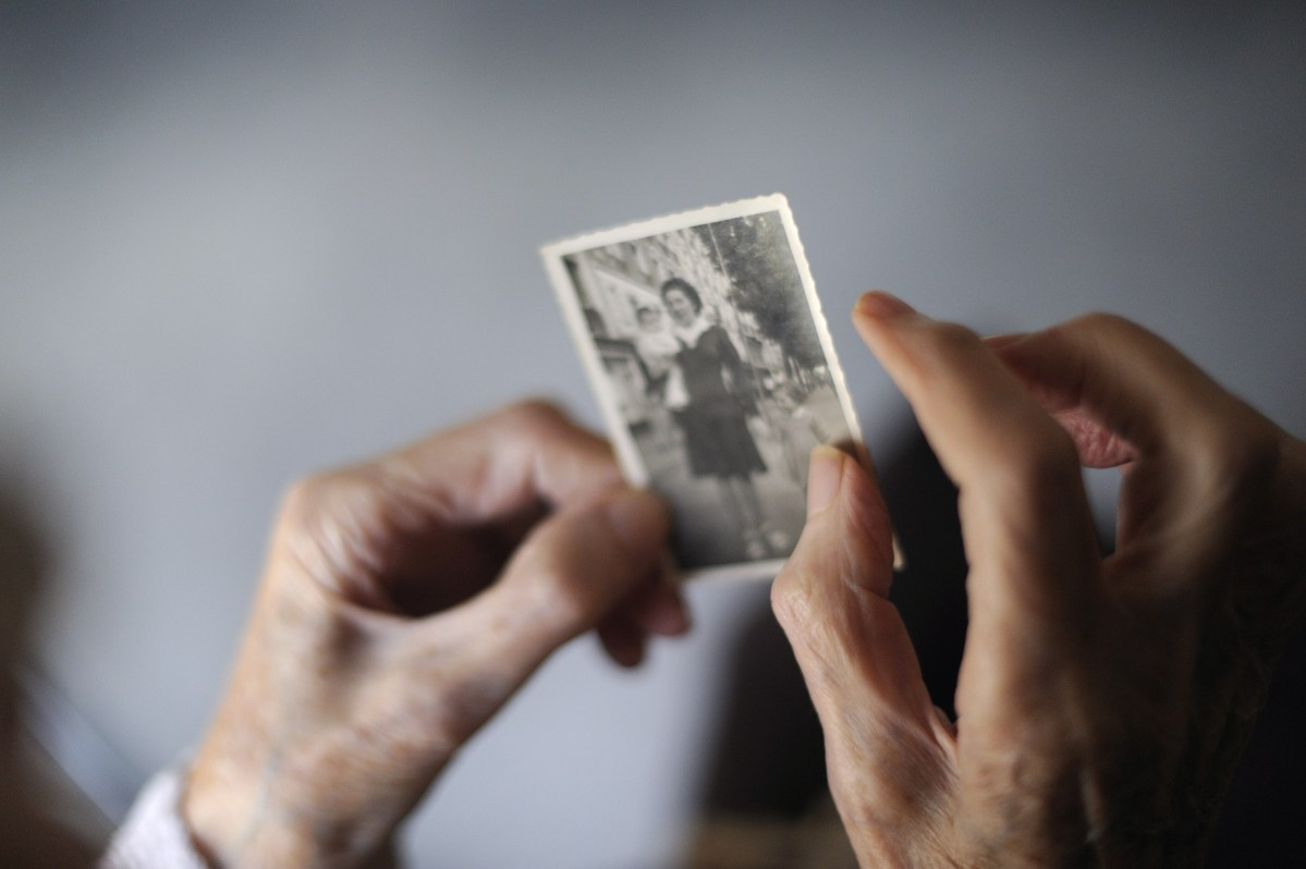 A woman, suffering from Alzheimer's disease looks at an picture of herself while living in a retirement house in eastern France.