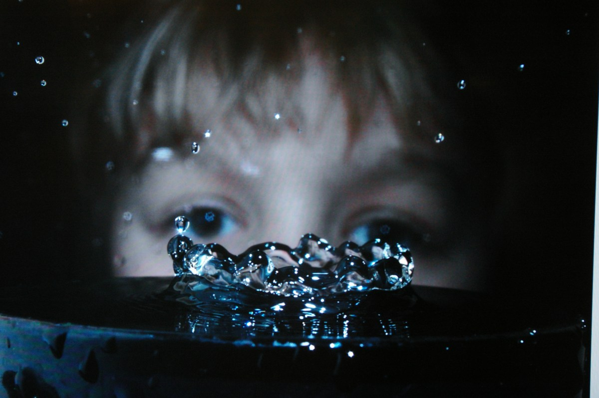 A child watches a drop of water.