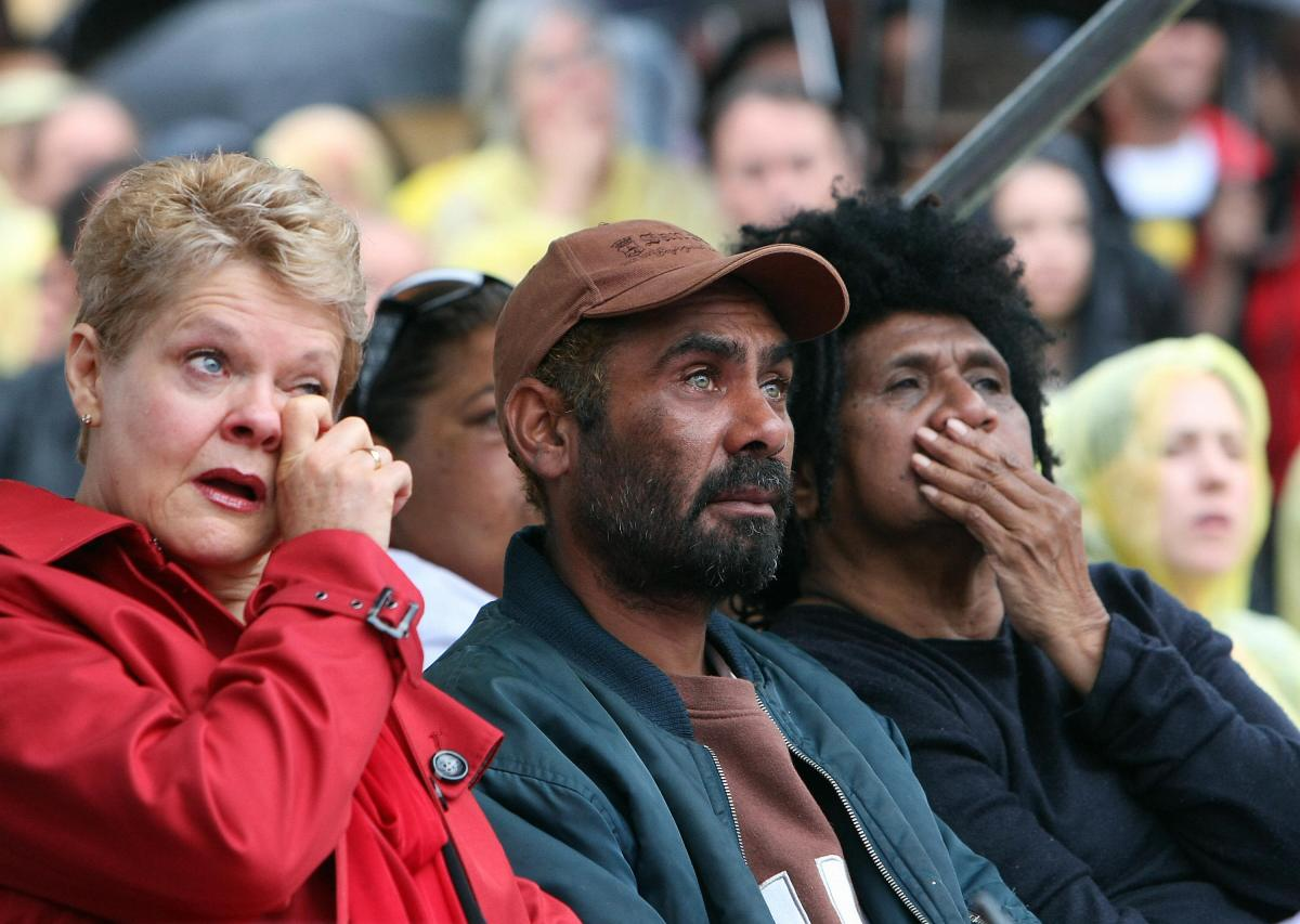 (L to R) Marcelle Hoff, Michael Kirby and Shireen Malamoo are overcome with emotion as they watch Australian Prime Minister Kevin Rudd on a large screen deliver an historic apology to Aboriginal people for injustices committed over two centuries of white settlement, at The Block Aboriginal community in Sydney on February 13, 2008. Of the million indigenous people who are believed to have lived throughout the country before white settlement began in 1788, there are only about 470,000 Aborigines left, just over two percent of Australia's population of 21 million. AFP PHOTO/Torsten BLACKWOOD (Photo credit should read TORSTEN BLACKWOOD/AFP/Getty Images)