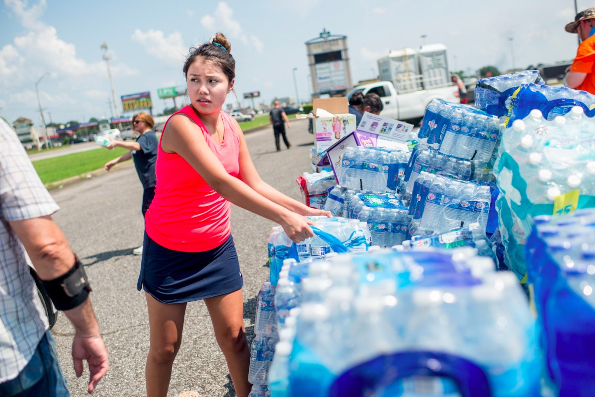 Volunteers help load cars with donated supplies outside Center Mall in Port Arthur, Texas on September 2, 2017. As floodwaters receded in Houston after Hurricane Harvey, nearby cities such as Beaumont which had lost its water supply — and Port Arthur struggled to recover. One week after Harvey slammed into southeast Texas as a Category Four hurricane, rescuers were still out searching for people still inside flooded homes.