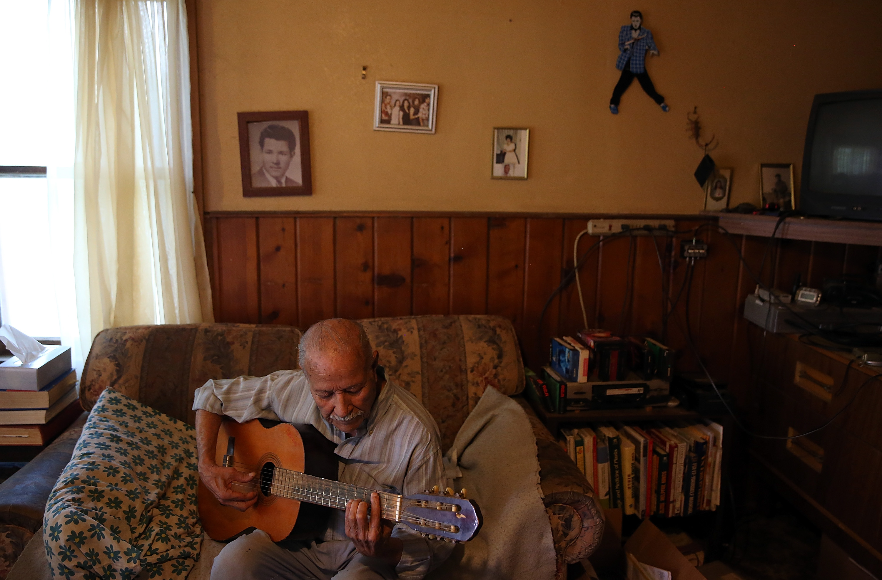 Porterville, California, resident Manuel Dominguez, who has no running water, plays guitar in his living room on April 23, 2015.