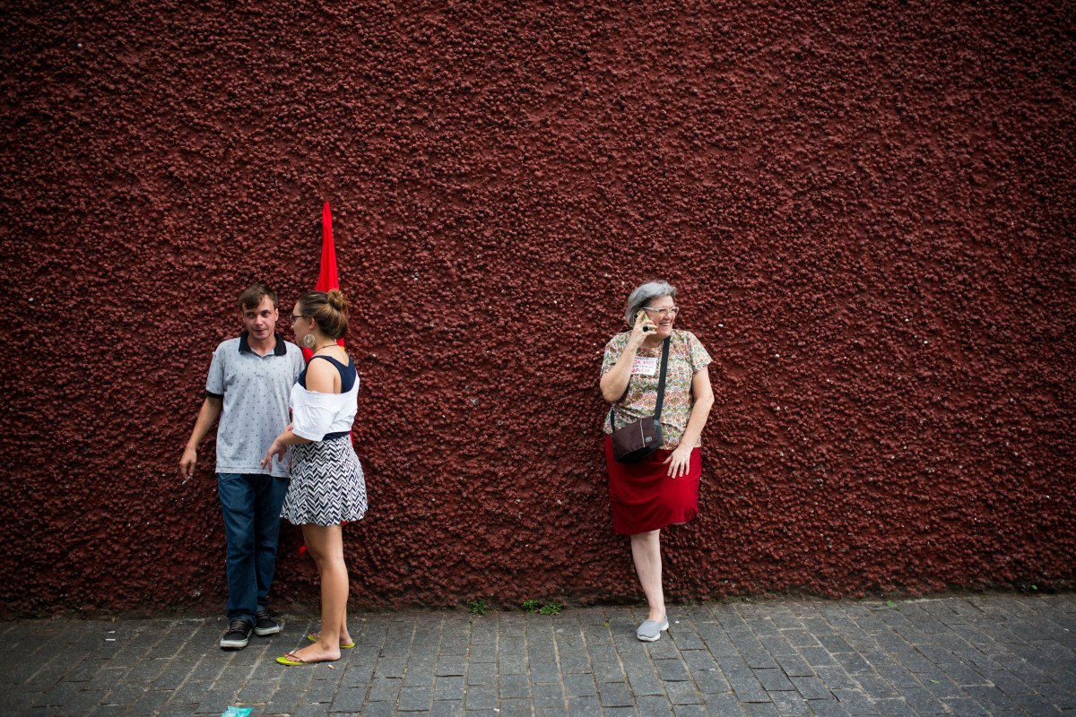 People chat outside a rally for the Former President of Brazil, Luiz Inacio Lula da Silva at the Partido dos Trabalhadores headquarters on March 4, 2016, in Sao Paulo, Brazil.