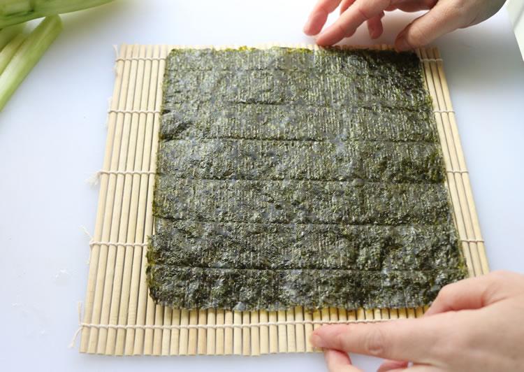 a seaweed nori sheet on a bamboo rolling mat for making sushi