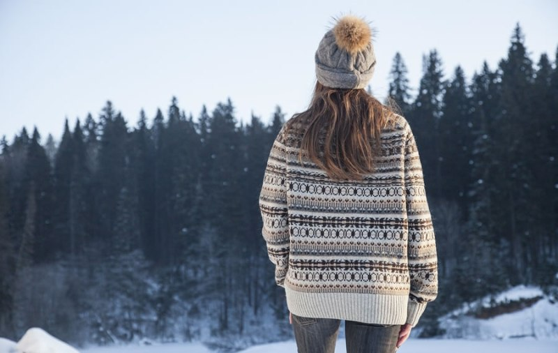 Woman with sweater and knit hat looking at snowy trees