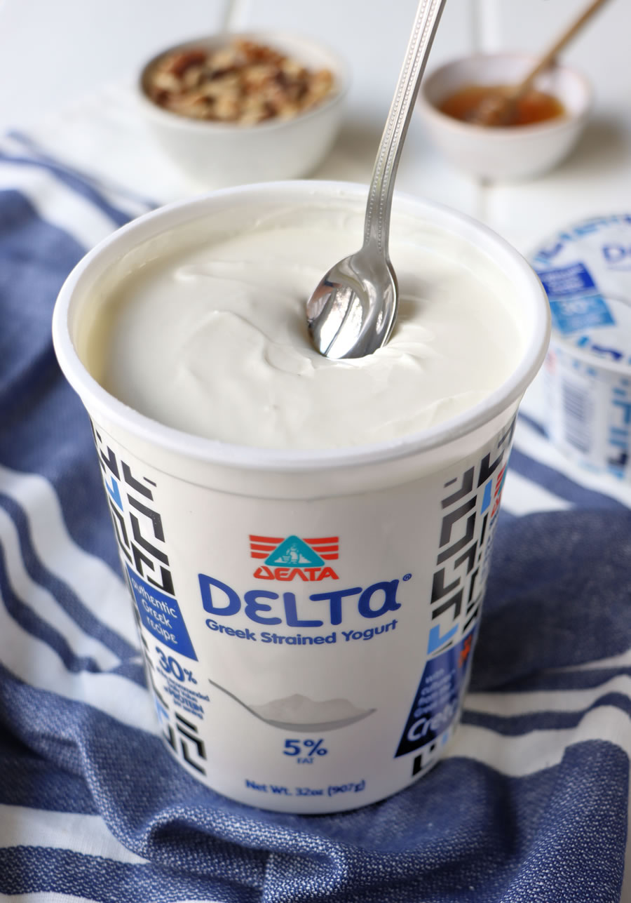 a spoon dipping into Delta Greek yogurt with walnuts and honey