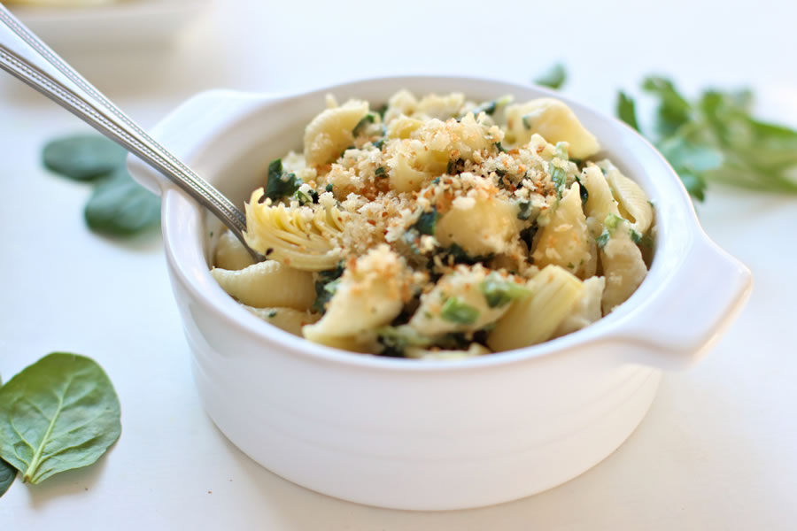 bowl of mac and cheese with spinach and artichoke
