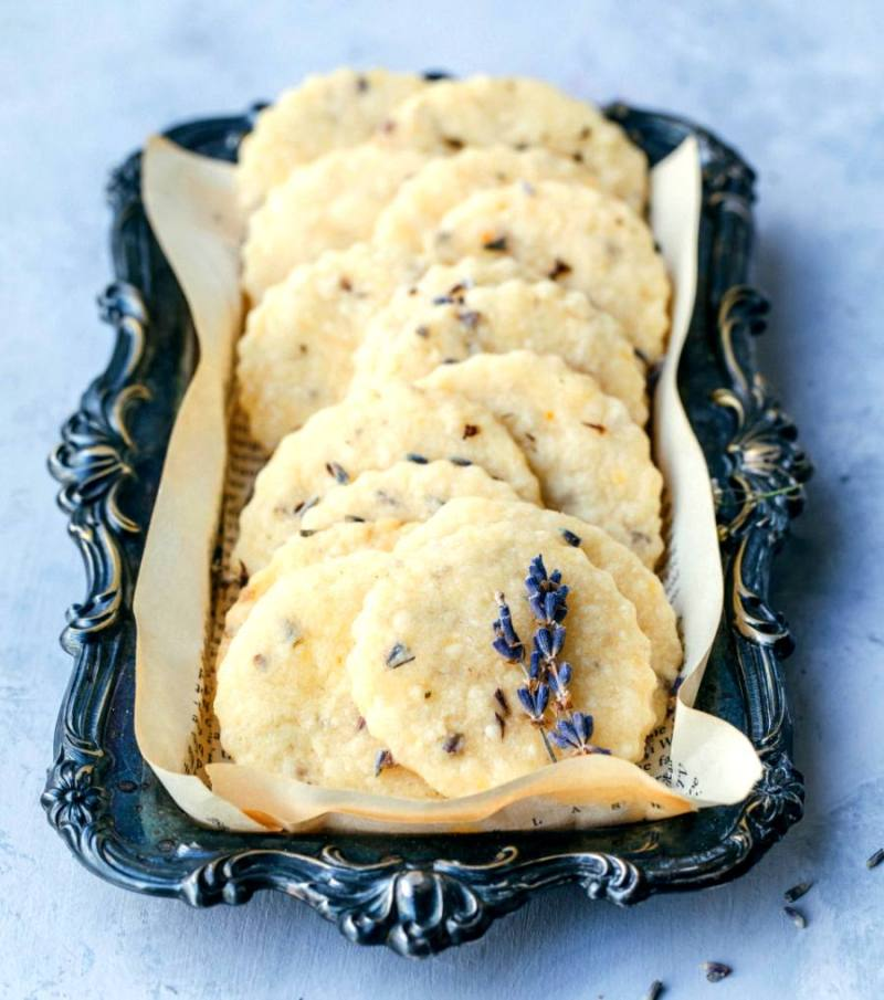 lavender shortbread cookies arranged on a scrolled rectangular antique plate with lavender sprigs