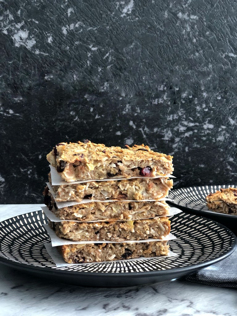 Fruit, oat and chia slices stacked on top of each other, on a black patterned plate against a black background.