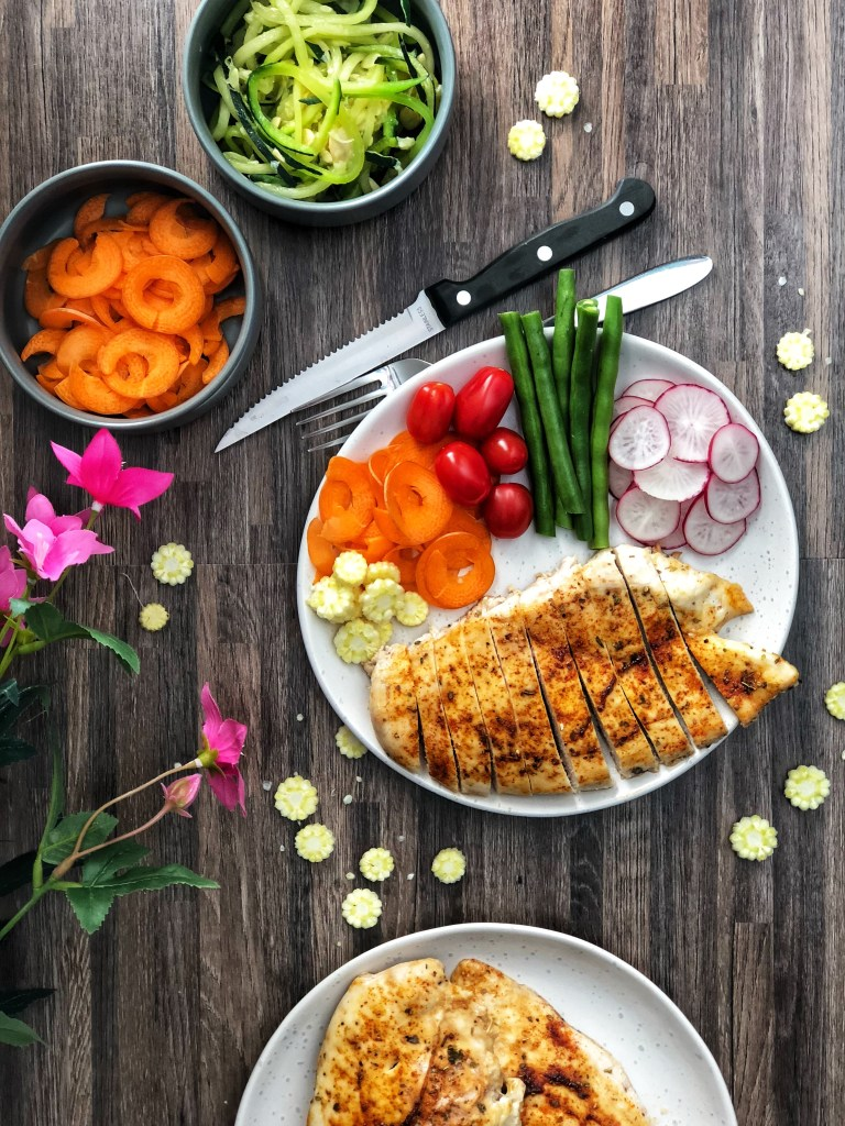 Juicy chicken breast on a plate with raw vegetables.
